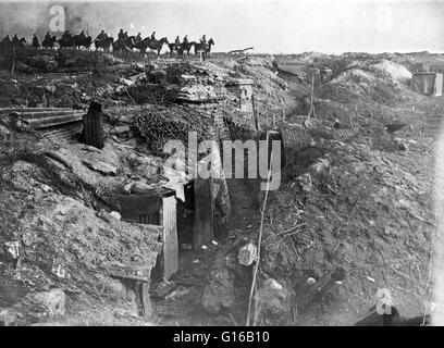 Abandoned British trench which was captured by the Germans; in background, German soldiers on horseback view the - Stock Photo