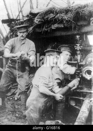 British soldiers loading a cannon or howitzer in a camouflaged bunker, 1915. The onset of trench warfare after the - Stock Photo