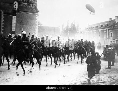 French soldiers on horseback in street, with an airship flying in air behind them during World War I. Cavalry or - Stock Photo