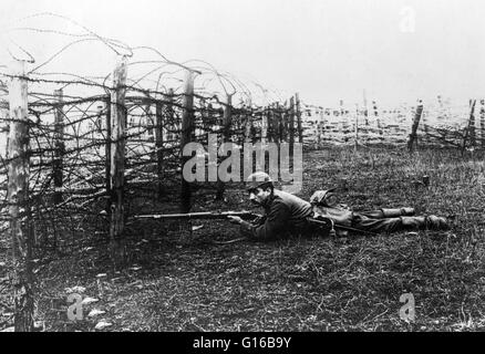 German sniper laying on ground near barbed wire defenses. Throughout World War I, snipers were often used in the - Stock Photo