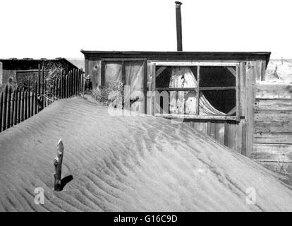Windblown sand blocks the door of a shed Cimarron County, Oklahoma. Piling up around a house one day, sand would - Stock Photo