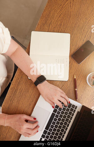 Top view of woman sitting at her desk and working on laptop. Businesswoman working from home. - Stock Photo