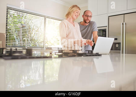 Indoor shot of a happy couple using laptop computer in the kitchen. Woman showing something on laptop to man. - Stock Photo