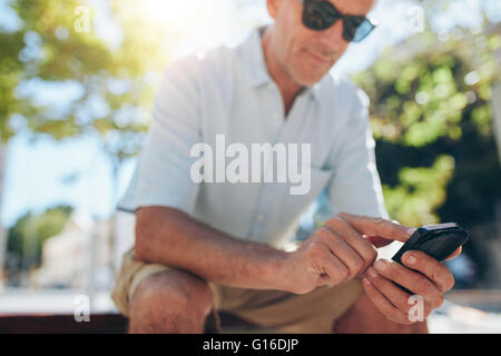 Close up portrait of senior man using cell phone while sitting on a bench in the city on a sunny day. Focus on hands - Stock Photo