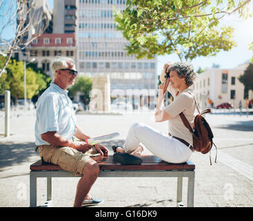 Side view of mature man sitting on bench and woman taking his photos with digital camera. Senior couple having fun - Stock Photo