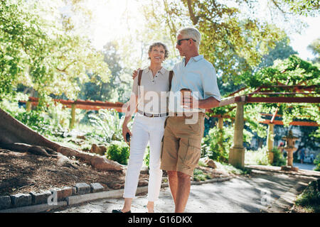 Full length portrait of an loving senior couple enjoying a walk in the park together. Tourist walking in a park. - Stock Photo