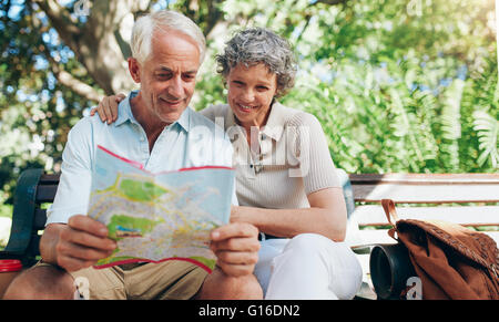 Happy mature couple using city map for direction. Retired couple on a vacation sitting outdoors on a park bench - Stock Photo