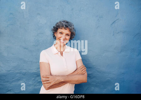 Portrait of attractive mature woman with her arms crossed standing against blue background. She is leaning to a - Stock Photo