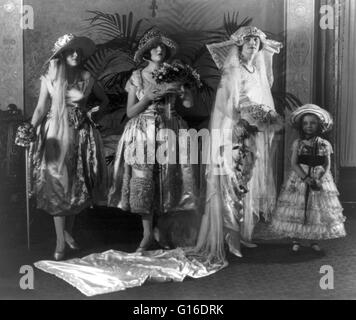 Woman in bridal gown posing with attendants. A wedding dress or wedding gown is the clothing worn by a bride during - Stock Photo
