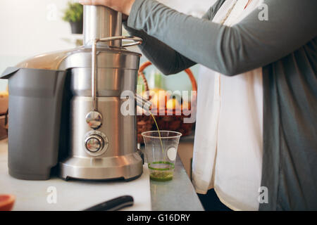 Cropped shot of  woman making fruit juice using juicer machine at bar counter. - Stock Photo