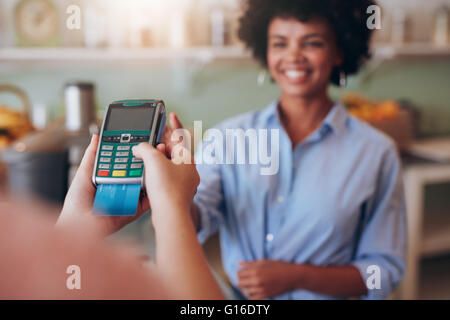 Female customer paying by credit card at juice bar. Focus on woman hands entering security pin in credit card reader. - Stock Photo