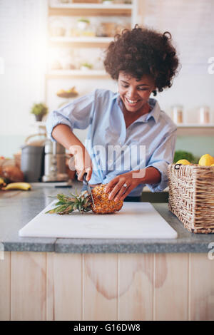 Young african woman standing behind bar counter cutting a pineapple on chopping board. Female working at juice bar - Stock Photo