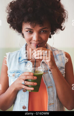 Portrait of attractive african woman drinking fresh fruit juice. Woman looking with glass of juice looking at camera. - Stock Photo