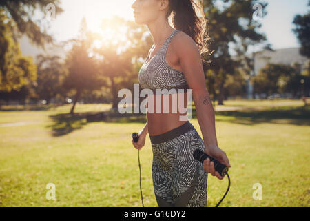 Outdoor shot of muscular and sporty woman skipping outdoors in nature. Fitness female working out with jump rope - Stock Photo
