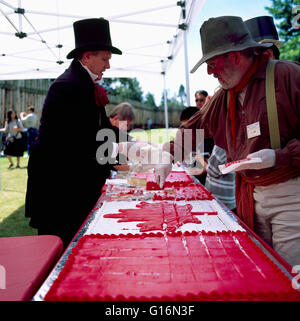 Celebrating Canada Day at Fort Langley, BC, British Columbia, Canada - Reenactors cutting Big Cake decorated as - Stock Photo