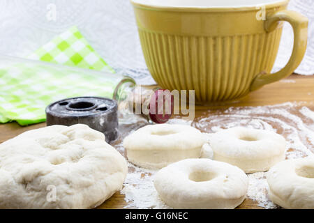 Risen dough nut dough on flowered wood table with vintage cutter and glass rolling pin - Stock Photo