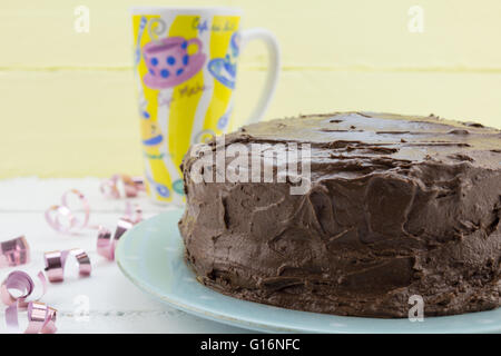 Chocolate cake with bright coffee mug and pink ribbons in background - Stock Photo