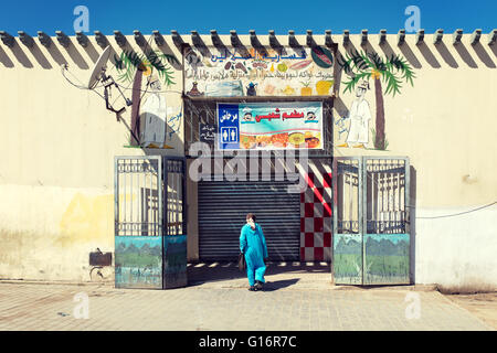 A woman wearing traditional clothes entering a market. Fez, Morocco. - Stock Photo