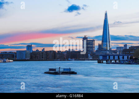 Modern London cityscape during sunset with a pink stripe in sky - Stock Photo