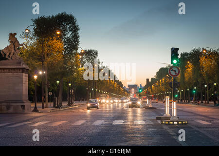 Crossing the Avenue des Champs Elysées with the Arc de Triomphe in the distance, taken at dusk. Traffic on the road - Stock Photo