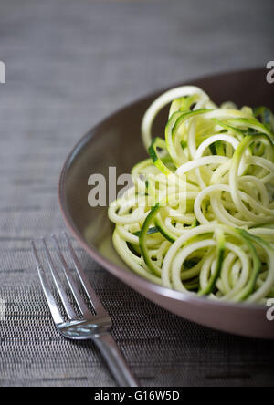 A bowl of courgette (Zucchini) noodles (spaghetti) made using a spiralizer - Stock Photo