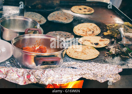 Traditional Mexican Gorditas - thick yellow or blue corn tortillas stuffed with cheese, veggies and meats, cooked - Stock Photo