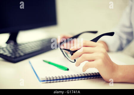 close up of hands with eyeglasses and notebook - Stock Photo