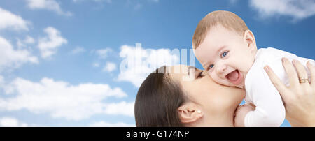 happy mother kissing her baby over blue sky - Stock Photo