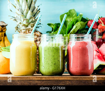 Freshly blended fruit smoothies of various colors and tastes  in glass jars. Yellow, red, green. Turquoise blue - Stock Photo