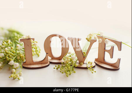 wooden word love with lilies and place for your text - Stock Photo