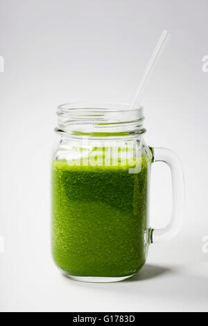 Healthy green smoothie with straw in a jar mug on white  - superfoods, detox, diet, health, vegetarian food concept - Stock Photo