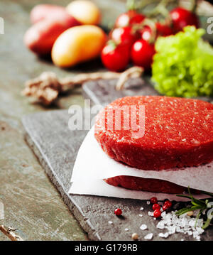 Raw Ground beef meat Burger steak cutlets with seasoning and vegetables on vintage wooden boards - Stock Photo