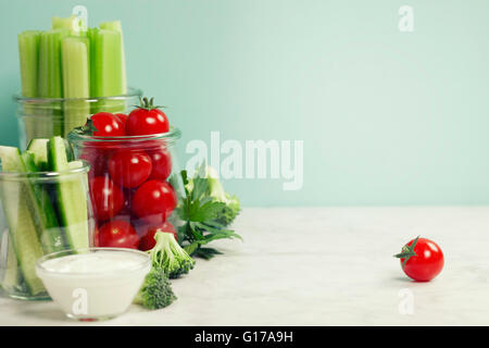 assorted fresh vegetables with dip on blue background - Vegan, Vegetarian, Healthy food - Stock Photo