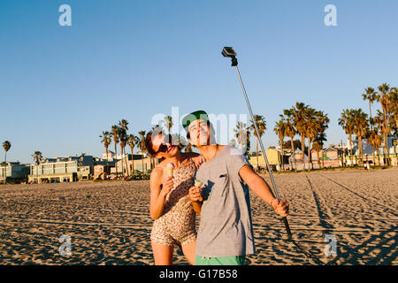 Young couple taking selfie with smartphone stick on beach, Venice Beach, California, USA - Stock Photo