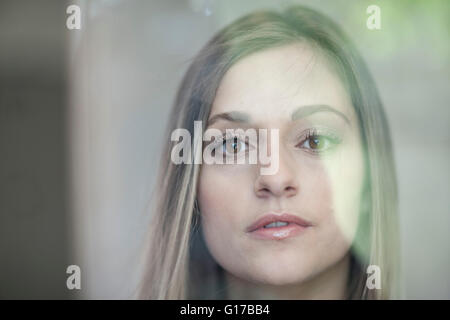 Young woman looking through glass, close-up - Stock Photo