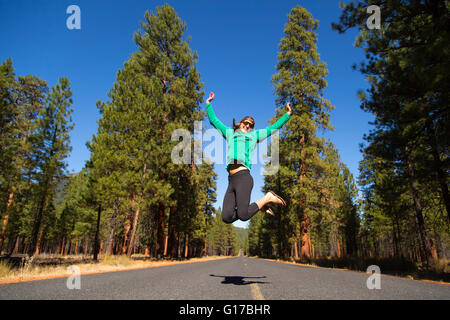 Young woman jumping mid air on forest road, Sisters, Oregon, USA - Stock Photo