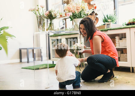 Mother crouching with son in flower shop, mother holding bouquet - Stock Photo