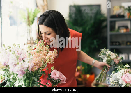 Florist smelling flowers in flower shop - Stock Photo