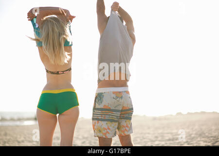 Rear view of couple on beach removing vests - Stock Photo