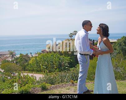 Honeymoon couple chatting on hill near ocean, Los Angeles, California - Stock Photo