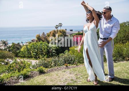 Honeymoon couple dancing on hill near ocean, Los Angeles, California - Stock Photo