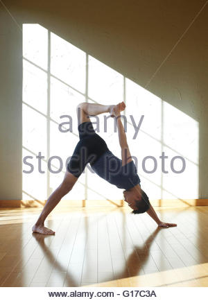 Woman doing yoga in studio, in one legged wheel position - Stock Photo