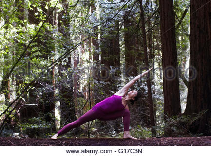 Mid adult woman doing yoga in forest, in extended side angle pose - Stock Photo