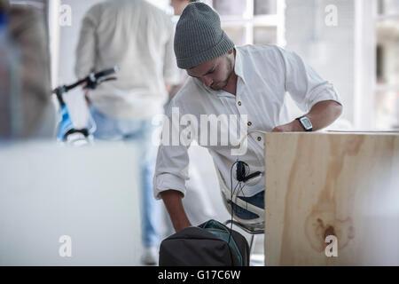 Businessman settling in at desk in loft office - Stock Photo