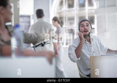 Colleague beckoning to another in loft office - Stock Photo