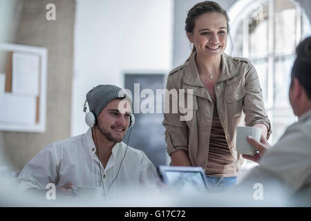 Colleague handing out coffee in loft office - Stock Photo