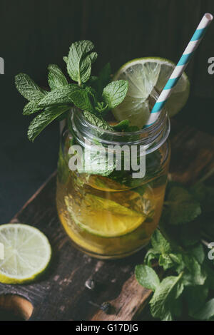 Ice green tea with ice, fresh mint, lime and lemon in glass mason jar with retro cocktail tube, served on wooden - Stock Photo