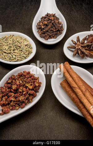 Five Spice Spoon Circle Cinnamon and Szechuan Peppercorns in foreground on slate cutting board - Stock Photo