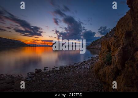 Bridge mainland to island Krk in Croatia in sunset twilight picturesque colorful landscape atmospheric clouds scenery - Stock Photo