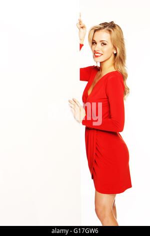 Attractive blonde woman in a smart red dress standing alongside a large vertical blank white card that she is holding - Stock Photo